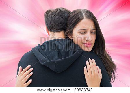 Unhappy brunette hugging her boyfriend against digitally generated girly heart design