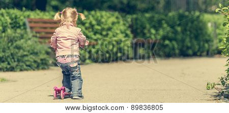Two years old girl riding her scooter on the park. back  view
