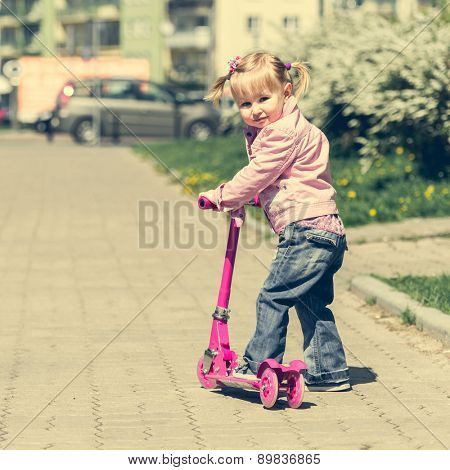 Two years old girl riding her scooter on the street