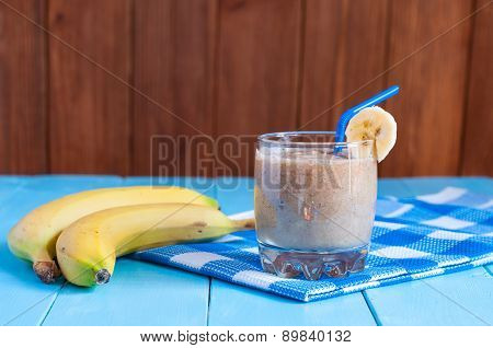 Chocolate milkshake smoothie in glass on light wooden background.