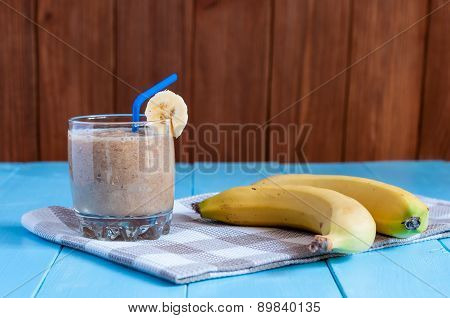 Healthy homemade chocolate banana smoothie in glass and fresh bananas on wooden background.