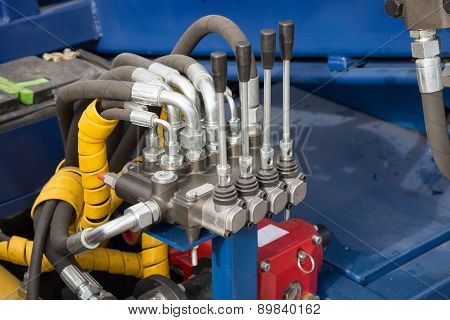 Hydraulic tubes, fittings and levers on control panel of mechani