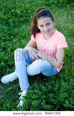 Little girl with blue eyes sitting at the garden