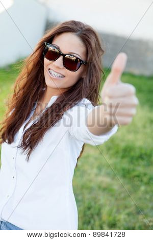 Brunette cool girl with sunglasses in the park saying OK