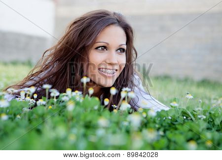 Brunette cool girl with brackets lying on the grass with many flowers