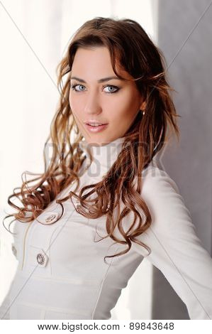 Portrait Of A Beautiful Brunette Girl Near The Wall