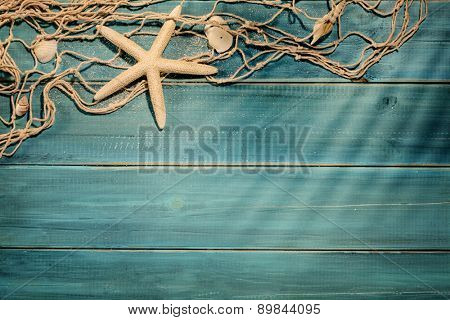 Aged deck with fish net and seashells