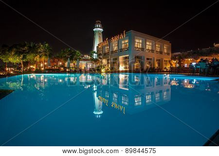 Night hotel building behind the pool.
