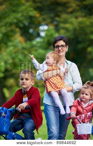 portrait of happy young family,  mother and  kids have fun in park