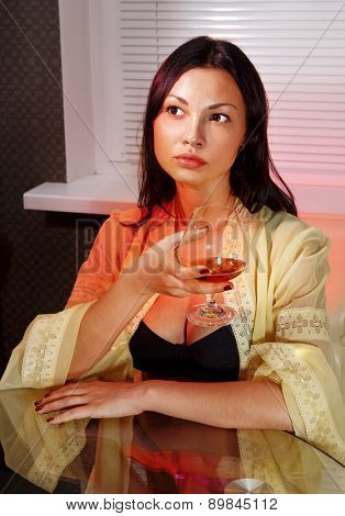 beautiful ladylove in dress on sofa with glass of brandy