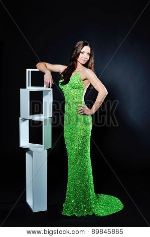Beautiful Brunette In Green Dress Posing On A Dark Background
