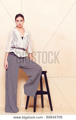 Full height portrait of a young woman in pantsuit