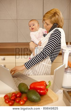 Young woman holding baby in arm, talking on phone, using laptop and tablet in kitchen.