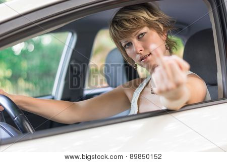 Young woman driving car and showing middle finger