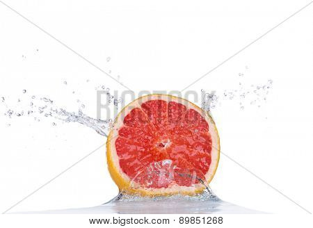 Fresh grapefruit in water splash isolated on white background