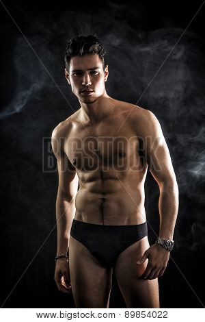 Handsome, fit young man wearing only underwear standing on black