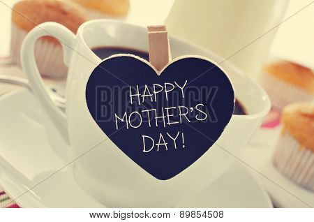 the sentence happy mothers day written in a heart-shaped blackboard placed in a cup of coffee, with some muffins in the background in a set table for breakfast