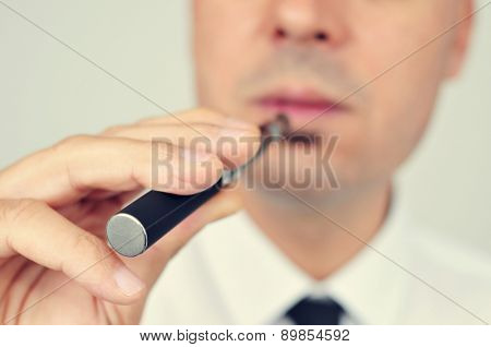 closeup of a young caucasian man wearing a white shirt and black tie vaping with an electronic cigarette