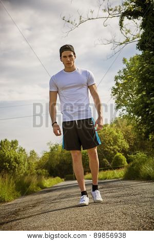 Handsome young man walking and trekking on road
