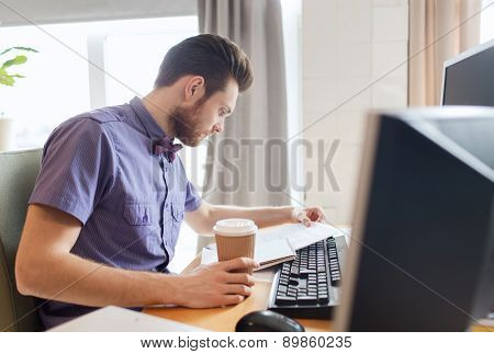 business, startup and people concept - businessman or creative male office worker drinking coffee and reading papers