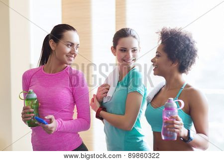 fitness, sport, training, gym and lifestyle concept - group of happy women with bottles of water in gym