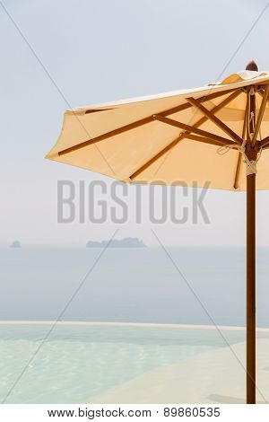 travel, vacation, tourism and luxury concept - beautiful view from infinity edge pool with parasol to sea