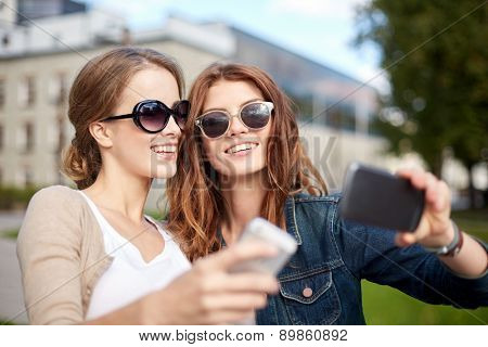 summer, technology, education and teenage concept - two happy students or teenage girls with smarphone taking selfie