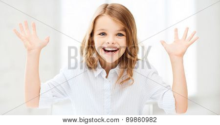 education and school concept - surprised and laughing little girl with raised hands at school or home