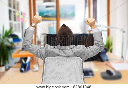 business, people, success and office concept - happy businessman sitting in chair with raised hands from back over office room background