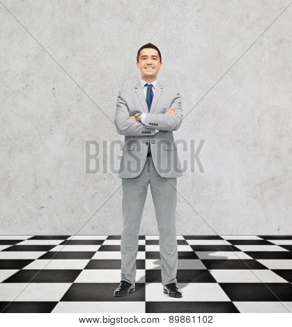 business, people and strategy concept - happy smiling businessman in suit standing on checkerboard pattern floor over gray background