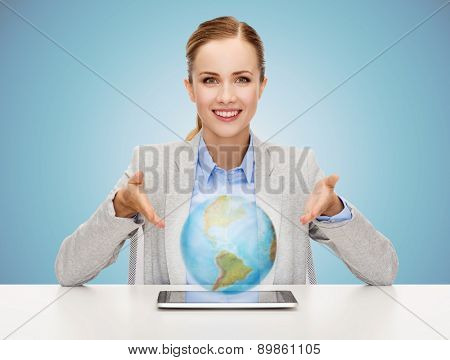 business, technology, education and people concept - smiling businesswoman sitting at table with tablet pc computer and globe hologram over blue background