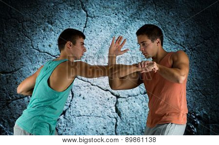 sport, competition, strength and people concept - young men fighting hand-to-hand over concrete wall background