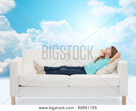 home, leisure, people and happiness concept - smiling little girl lying on sofa and dreaming over blue sky and white clouds background