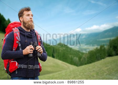 adventure, travel, tourism, hike and people concept - man with red backpack and binocular over alpine hills background