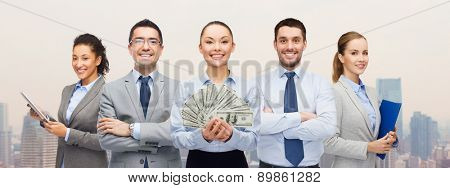 business, success and finances concept - group of smiling business people with dollar cash money over city background