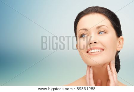 beauty, people and health concept - beautiful young woman touching her face and neck over blue background