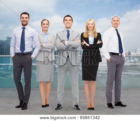 business, people, gesture and office concept - group of smiling businessmen over city background