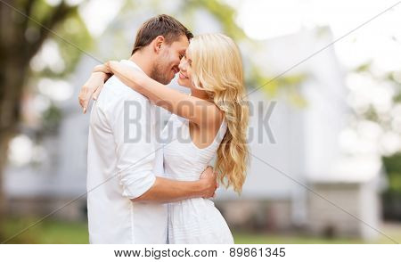 home, real estate, people, love and dating concept - happy couple hugging over summer house background