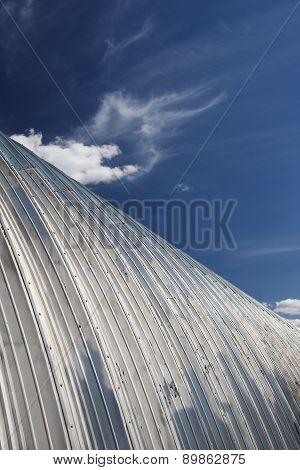 Metal Hangar Roof Against The Blue Sky