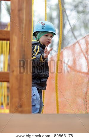 Child With Helmet Climbing On Rope