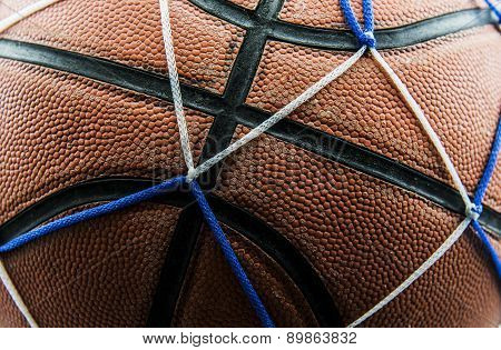 Close up old basketball ball in a net.
