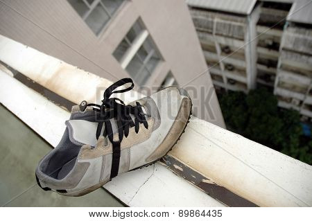 Leftover Shoe At The Edge Of A Building Roof