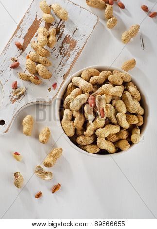 Peanuts In Shells Ona  White Wooden Background.