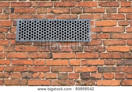 Brick wall with old iron ventilation plate