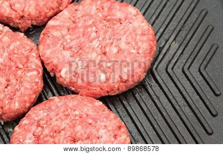 Raw burgers on a metal griddle