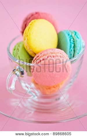 Colorful French Macaroons In Glass Cup On Pink Background