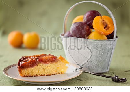 Slice Of Homemade Upside-down Plum Cake On Plate, With Fresh Plums On Background
