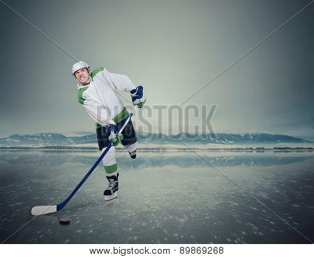 Young male hockey player on the frozen lake