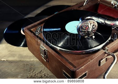 Gramophone with vinyl record on wooden table, closeup