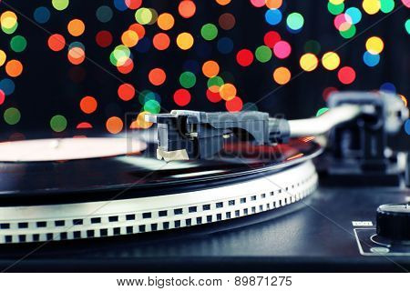 Gramophone with a vinyl record on colorful blurred background